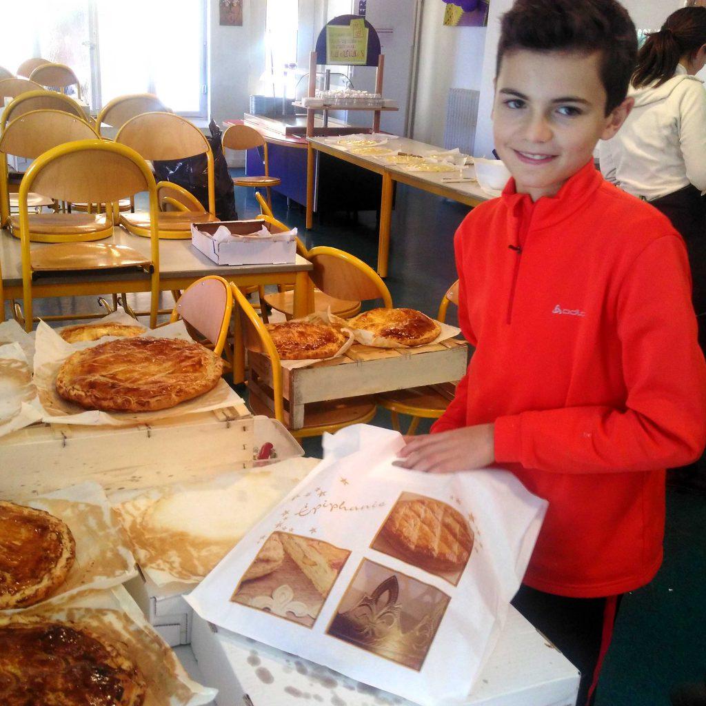 Jeune garçon bénévole participant à l'emballage des galettes des rois